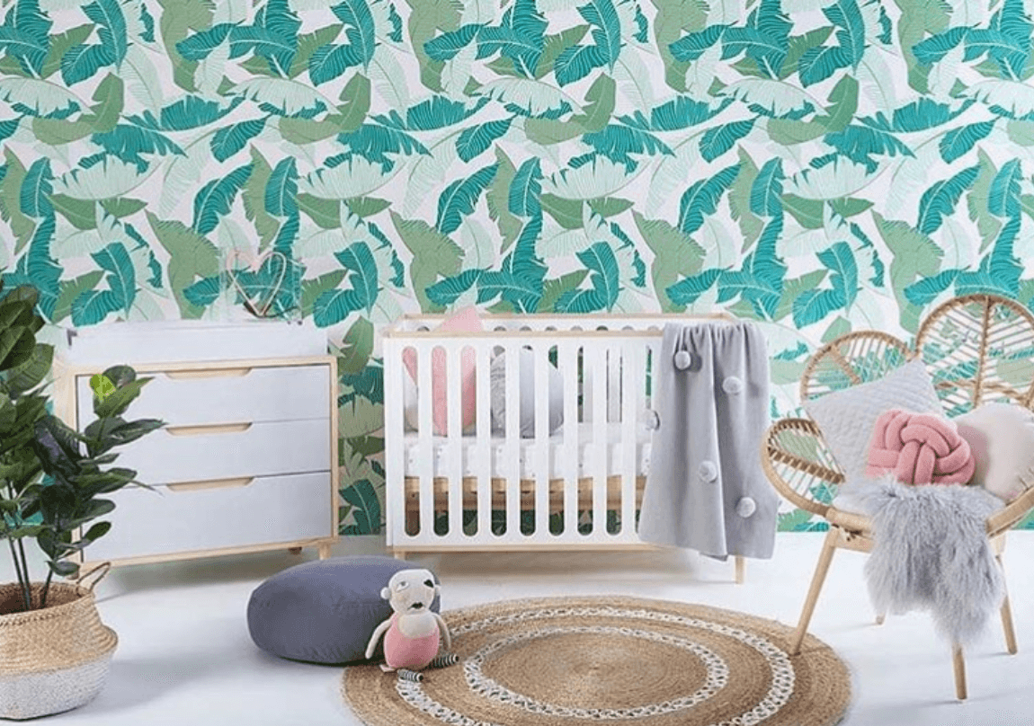 tropical green wallpaper in baby's room with crib